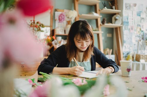 Glad Asian florist writing in notebook in flower shop