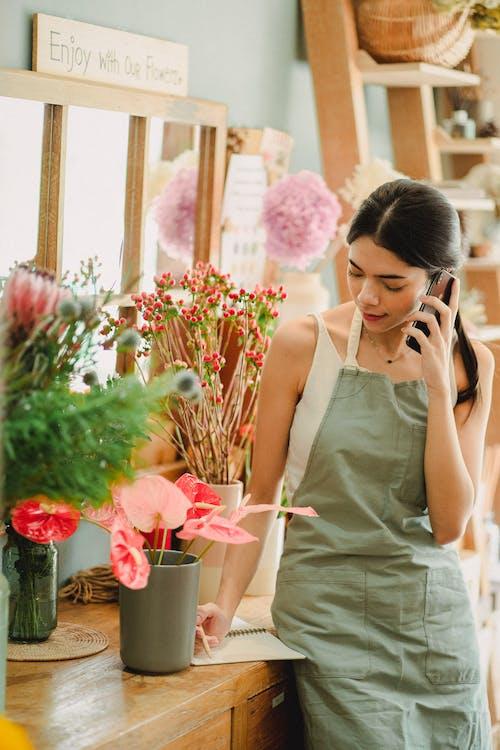 Toko Bunga Wanita Berbicara Di Telepon Dan Menulis Catatan Di Toko
