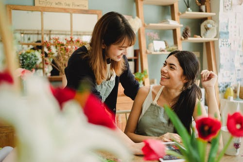 Joyful diverse female colleagues chatting in floral shop