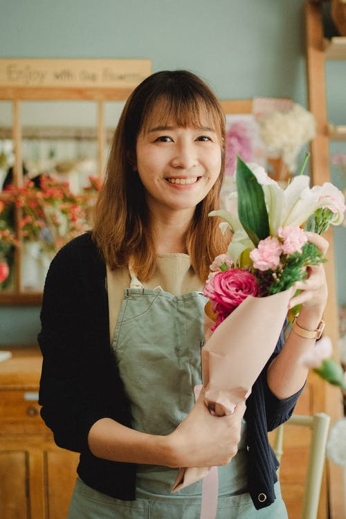 Attractive positive Asian female wearing green apron standing with wonderful bouquet in hands and looking at camera while working in light florists shop