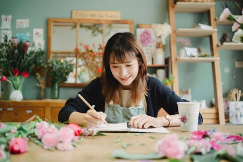 Smiling Asian woman writing in notebook in creative floral shop