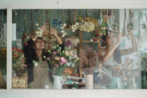Through window content multiracial female floral shop workers wearing aprons decorating store window with delicate flowers