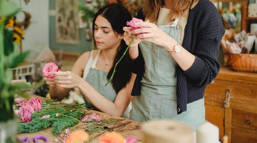 Positive young female florists wearing aprons removing leaves from flower stems before arranging bouquet in modern floristry store