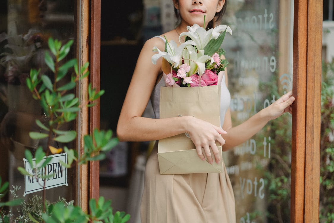 Crop young woman leaving floral shop with tender bouquet