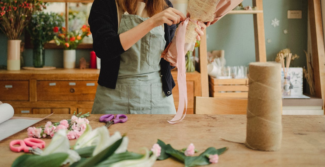 Crop unrecognizable female florist wearing apron standing near table in contemporary light floristry shop and arranging bouquets