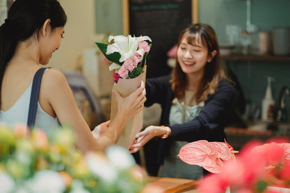 Happy Asian florist selling bouquet to female customer