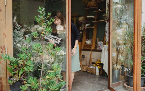 Positive young Asian female florist in apron standing near entrance and turning signboard on glass wall while working in modern floristry shop