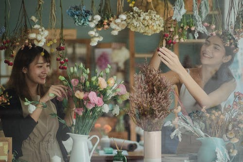 Happy smiling multiracial female colleagues working together in fragrant floristry store and decorating shop window with tender flowers