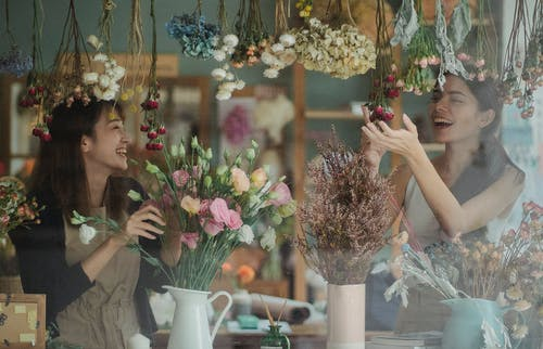 Joyful female florists working together in floral store