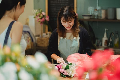 Content Asian female florist wearing light green apron composing tender bouquet for positive female customer while working at counter in floristry shop