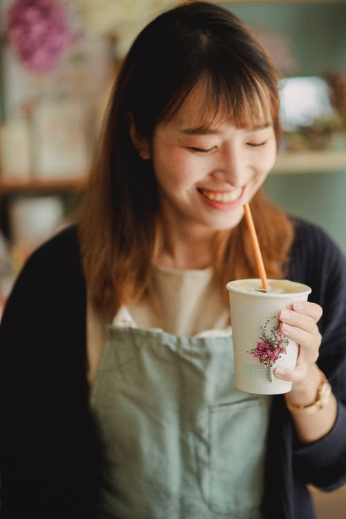 Delighted Asian woman in apron enjoying drink from paper cup
