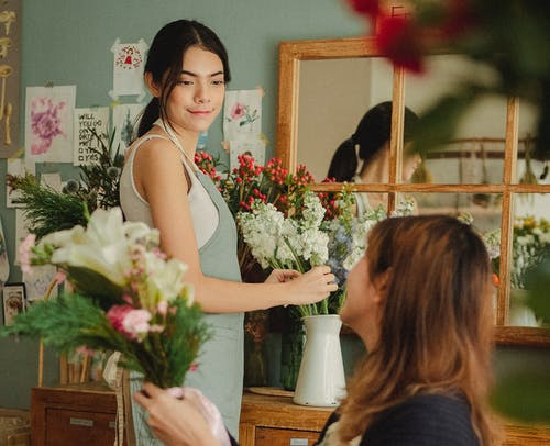 Side view glad young female florists wearing aprons arranging delicate flowers and looking at each other contentedly while working together in light floral store