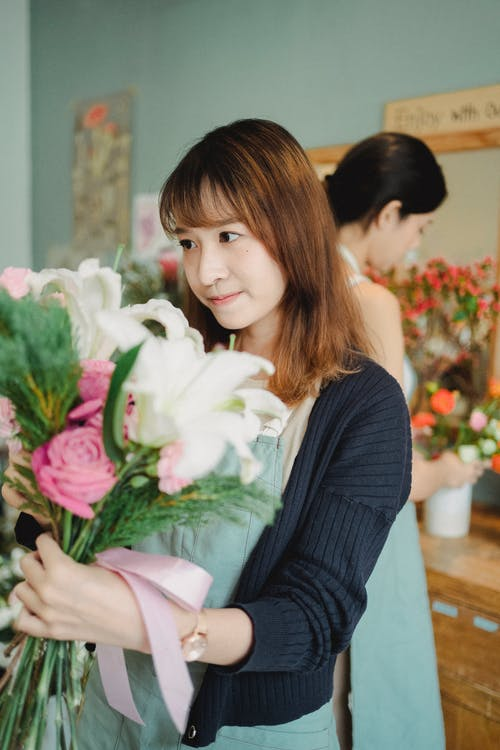 Charming Asian florist standing with bouquet in floral shop