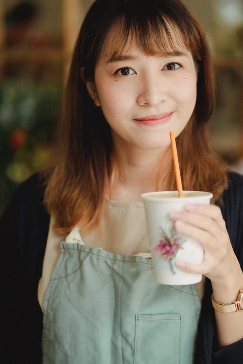 Crop glad young Asian female wearing light green apron enjoying refreshing drink from paper cup and looking at camera