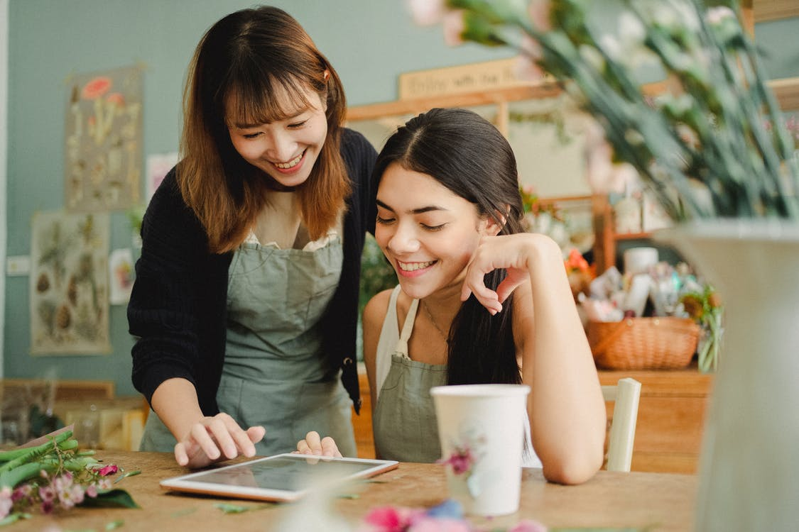 Smiling diverse female florists browsing tablet at work
