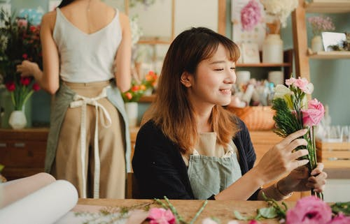 Happy smiling Asian female florist in apron sitting at table and composing blooming bouquet while working in light floral store near colleague