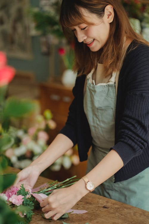 Crop smiling Asian florist making bouquet in floral shop