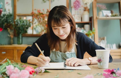 Glad young Asian female in uniform taking notes in notebook while working in light floral shop and sitting at table covered with many flowers petals