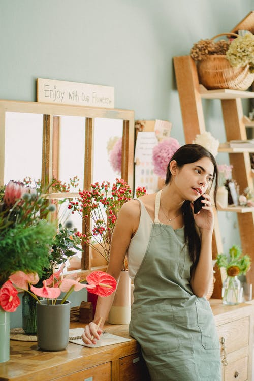 Pensive florist talking on mobile phone in shop
