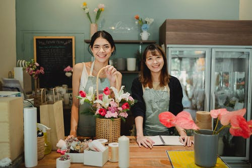 Smiling florists standing at counter in floristry shop