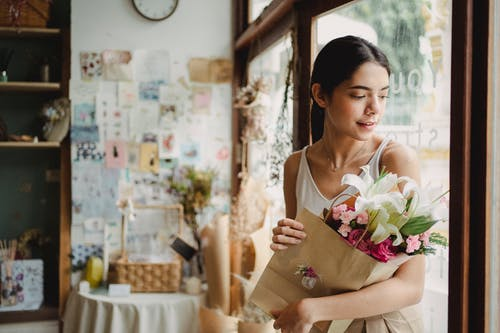 Tranquil female in casual clothes with paper bag with bouquet of fresh flowers leaving floristry store with cozy interior in daytime