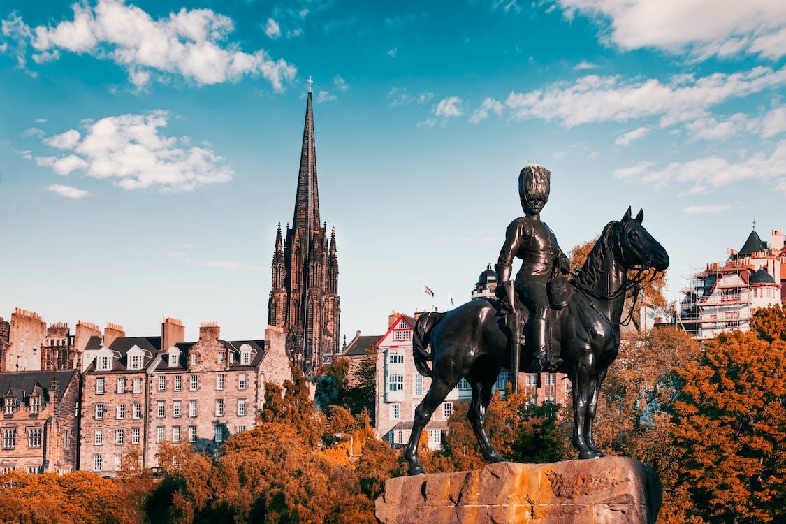 Black Statue of Man Riding Horse Near Brown Concrete Building