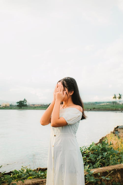 Unrecognizable woman covering face with hands on river shore