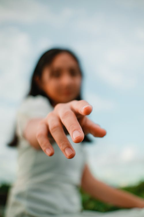 Unrecognizable ethnic woman reaching arm in daylight