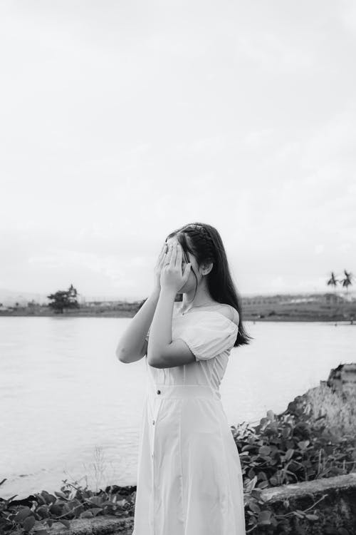 Black and white of unrecognizable lady in stylish apparel covering face with hands on river shore under cloudy sky