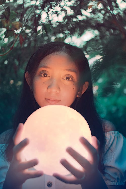From below of attentive Asian adolescent with glowing crystal ball looking at camera in park