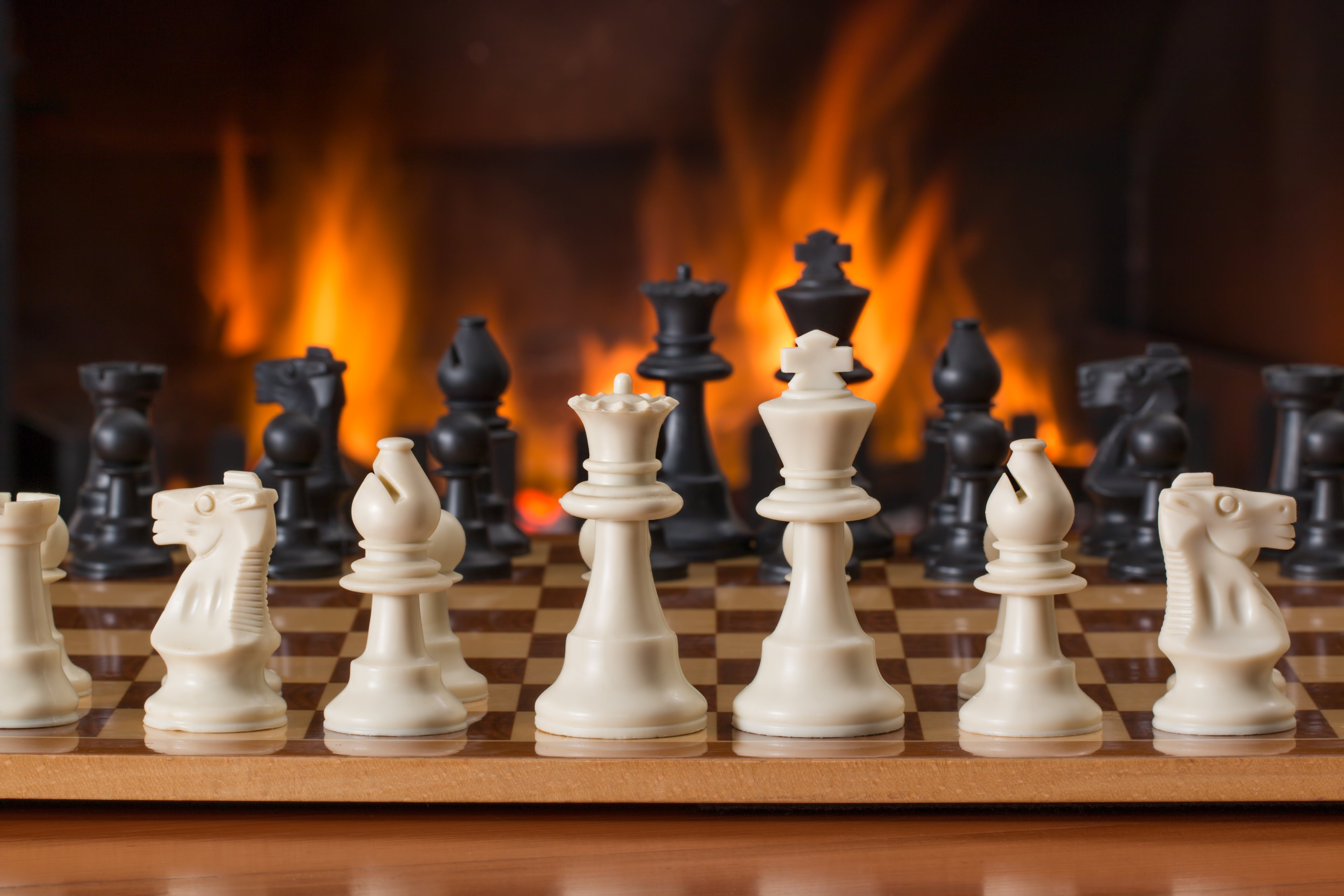 White and Black Chess Pieces on Board in Front of Fireplace