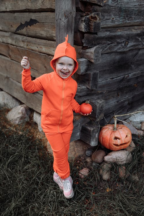 Child in Orange Long Sleeve Shirt and Red Hat Holding Pumpkin
