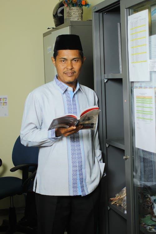 Man in White Dress Shirt Holding Brown Book