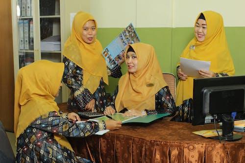 Woman in Yellow Hijab Sitting Beside Woman in Yellow Hijab