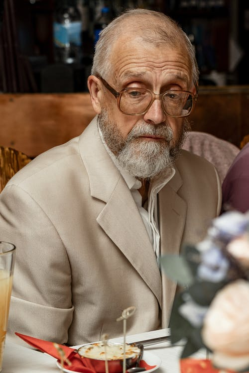 Wistful elderly man sitting at dining table in restaurant