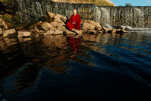Man in Red Jacket Sitting on Rock in River