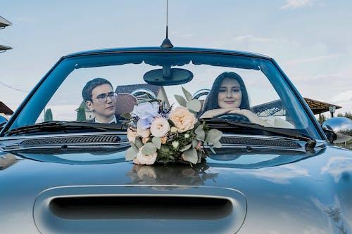 Happy newlyweds sitting in modern cabriolet