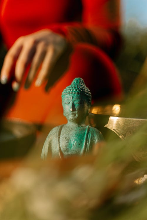 Blue Ceramic Buddha Figurine on Brown Wooden Table