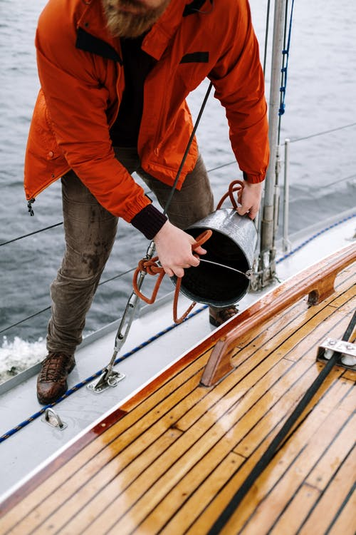Man in Orange Jacket and Gray Pants Holding Black and Red Fishing Rod