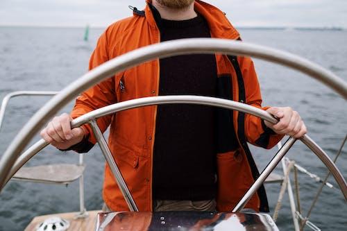Man in Orange and Black Jacket Holding White Boat Wheel