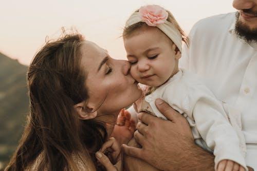 Padres Felices Abrazando Y Besando Al Bebé