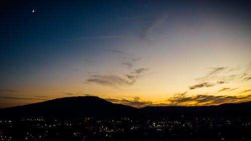 Безкоштовне стокове фото на тему «вечір, вода, гора, з підсвіткою»