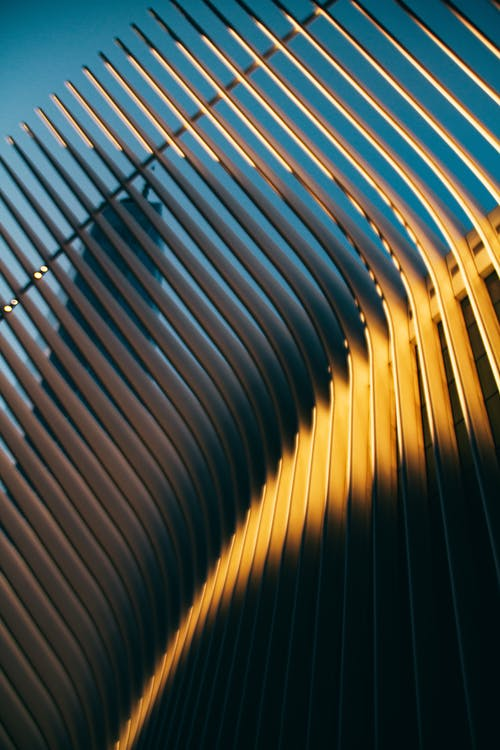 Low angle textured background of contemporary geometric fence with wavy beams in city under blue sky