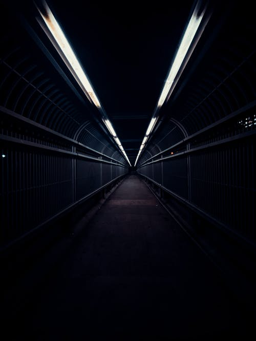 Long empty narrow walkway with fences and glowing lights in city at night