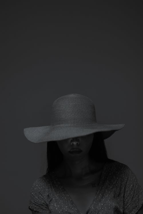 Sad woman in stylish hat covering eyes