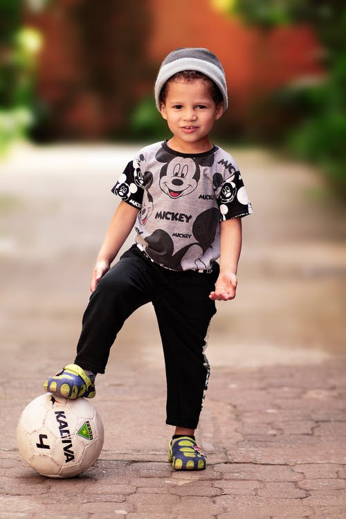 Cool kid standing with football ball