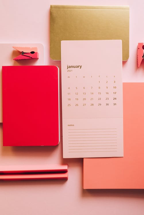 Flat lay of pink sheet with January month calendar and pink notepads with pins