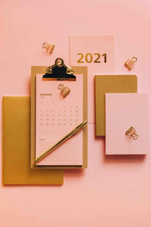 From above minimalistic composition of clipboard with calendar surrounded modern stationery on pink background