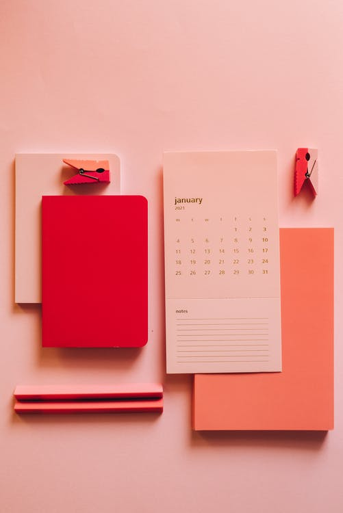 From above minimalistic composition of calendar paper with pink notebooks on pink background