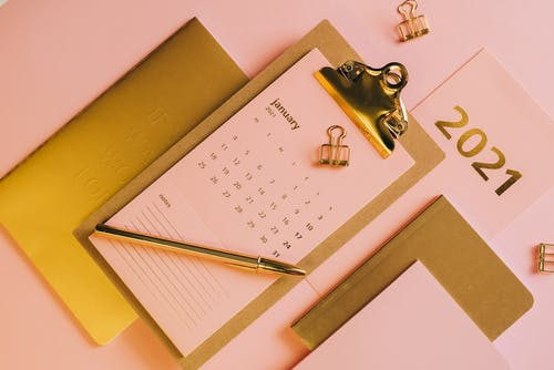 From above stylish workplace consisting of clipboard with calendar and golden notebook on pink background
